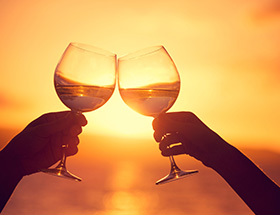 Couple clinking wineglasses at sunset