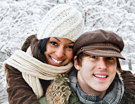 Happy black woman and white man in a winter park